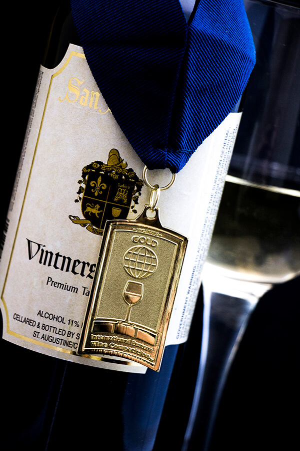 Bottle of Vintners Red with a gold competition medal around the neck